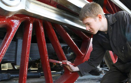 Jason Brown applies a coat of paint to the wheels of locomotive Dominion of Canada in the workshop at Locomotion.