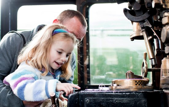 A parent and child sit in the cab of a steam locomotive
