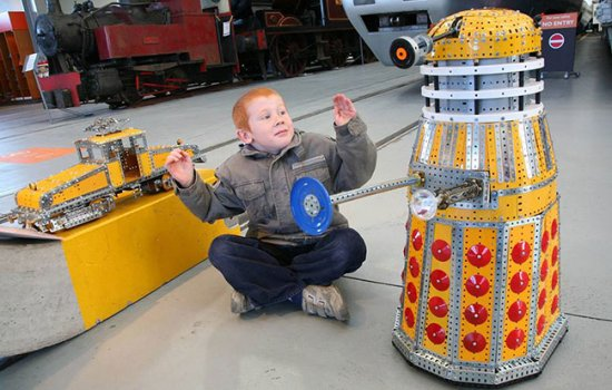 A young boy sits next to a Meccano Dalek