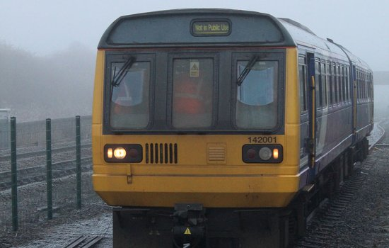 A yellow and blue Pacer train on a frosty railway line
