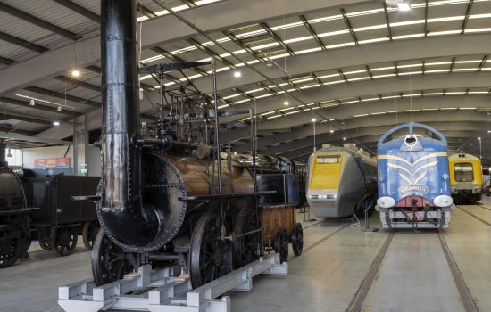 A large museum space with several locomotives