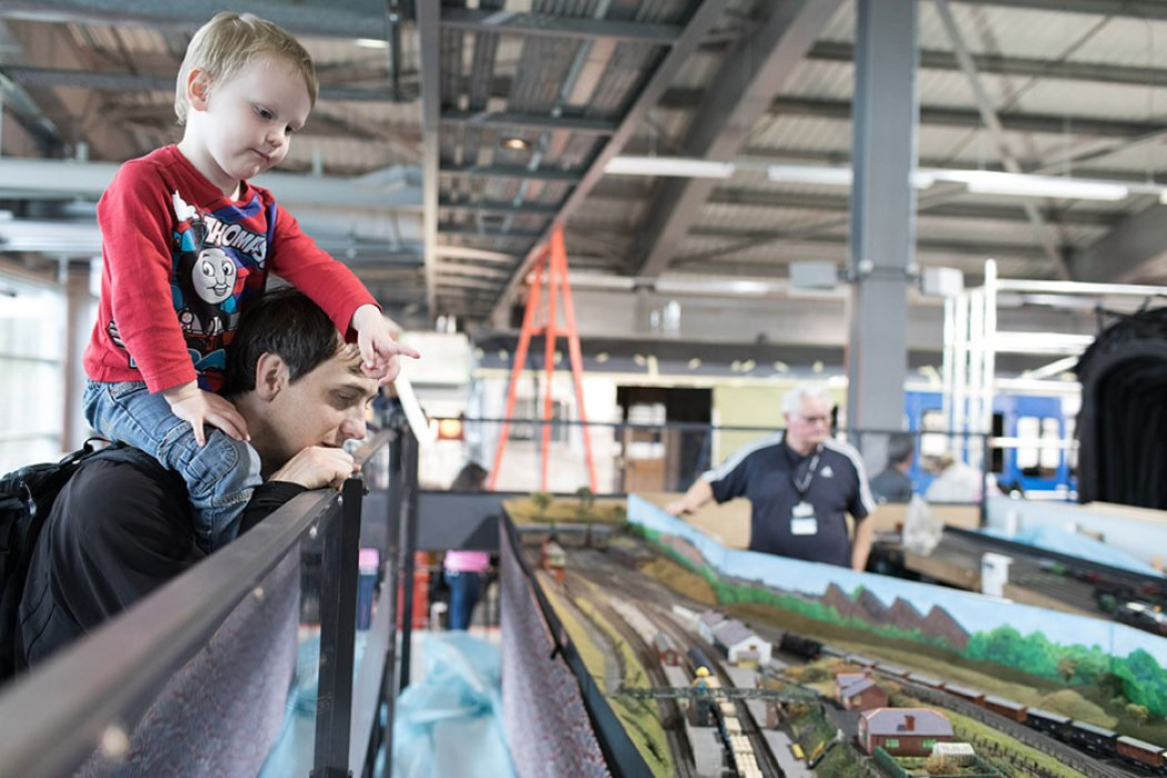 A parent and child look at the model railway at Locomotion