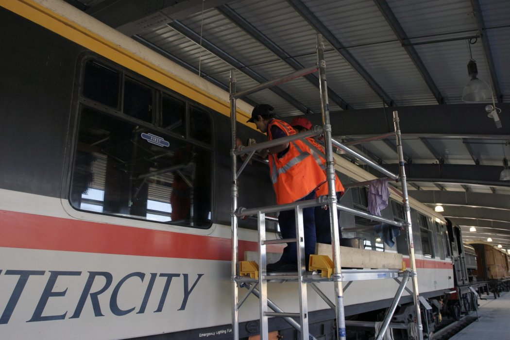 Conservation Assistants stand on scaffolding to clean the top of a BR Intercity railway carriage