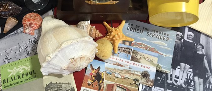 An assortment of objects from the seaside, including shells and picture postcards