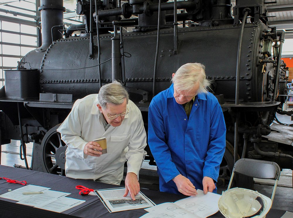 Two older white men stand in front of a locomotive looking at documents